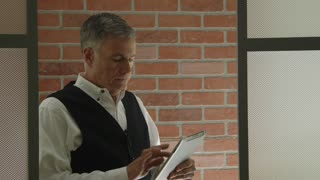 businessman standing in his office doorway looking at a tablet pc