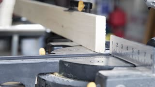carpenter cutting baseboard on a miter saw 4k
