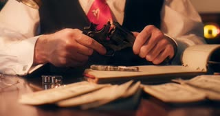closeup 40s gangster checking pistol and putting it on the desk 4k
