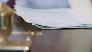 closeup businessman opening folder and writing on legal documents