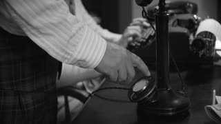 Closeup Of Man Dialing A Vintage Candlestick Phone Woman Typing In The Background