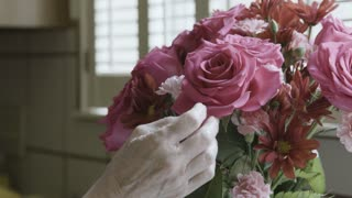 closeup of older womans hands adjusting flowers in a vase