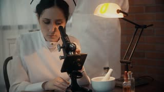 closeup of period nurse using a microscope takes notes color version