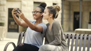 college girls taking selfies while sitting on a campus bench 4k