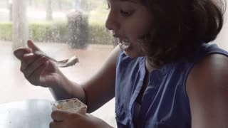 Cute Little Girl Eating Dessert In A Restaurant