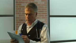 doctor writing in patients chart and looking at vitals