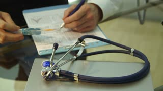 doctor writing in patients chart focus on stethoscope