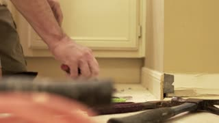 dolly contractor removing old baseboard from a wall 4k