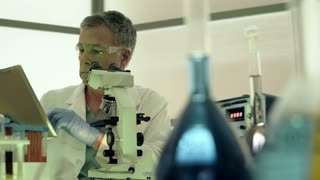 dolly scientist putting sample under microscope 4k