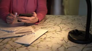 dolly woman paying bills using a smart phone 4k
