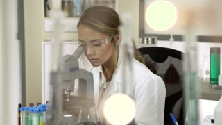 dolly young female scientist using a microscope in a lab 4k