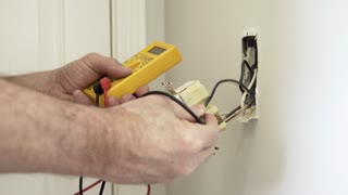 electrician checking voltage on a ground fault outlet wide 4k