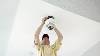 electrician finishing the wiring of a ceiling fan installation 4k