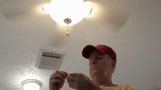 electrician placing the pull chains on the ceiling fan 4k