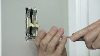 electrician removing an old toggle wall switch 4k