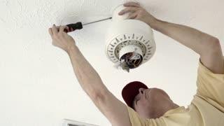 electrician tightening the screws on the ceiling fan shroud 4k
