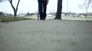 ground view of older woman walking with a cane on a sidewalk 4k