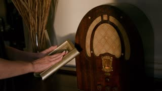 Hands of old woman lovingly holds picture frame by old radio
