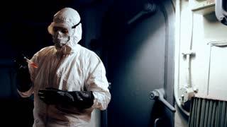 hazmat doctor looking at liquid in a vial