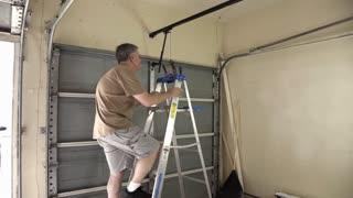 home handyman checking the belt on a garage door opener 4k