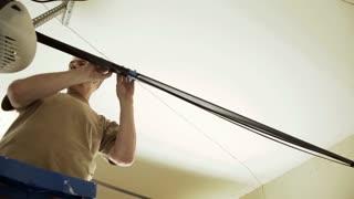 home handyman tightening the belt on a garage door opener 4k