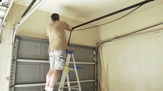 homeowner replacing the belt on hir garage door 4k
