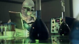 laboratory scientist in hazmat gear looking in a microscope 4k