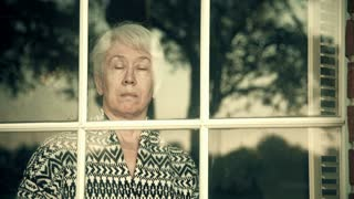 looking in from a window to a worried older woman 4k