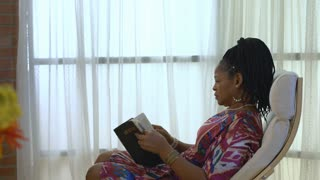 Lovely African American Woman Spends Quiet Time With Her Bible