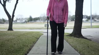 lower view of older woman walking with a cane on a sidewalk 4k