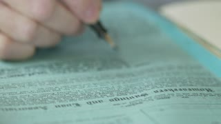 macro shot of businessman writing on a legal document focus on foreground