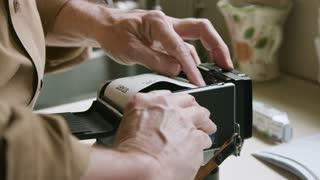 man loading film in a vintage medium format camera