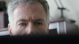 man looking over a laptop leans forward closer to screen