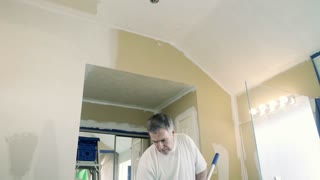 man painting the ceiling of a bathroom 4k
