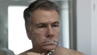 middle age man wiping his face after shaving in the morning 4k