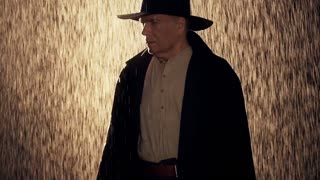old west cowboy in a thunderstorm shows pistol