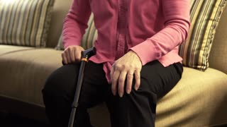 older woman in pain rubbing her knee 4k