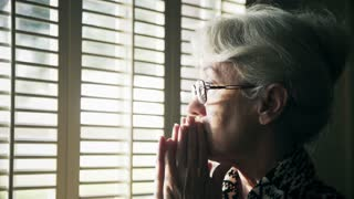 older woman looking out the window looks worried 4k
