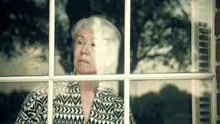 older woman standing next to a window happy to see someone 4k