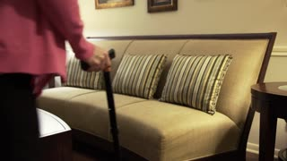 older woman walking with cane sits on her couch and rubs painful knee 4k