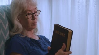 Older Woman with glasses reading from Holy Bible