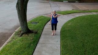 overhead pull back shot of woman walking on a sidewalk