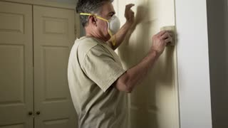 painter sanding the molding around a door 4k