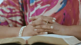 Pan up from praying hands on Bible to face of woman