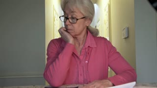 pull back from worried woman writing checks for her bills 4k