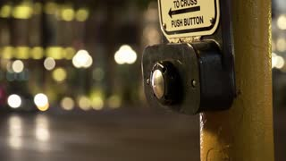 push button of a crosswalk sign of a busy street at night 4k