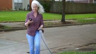 retired woman watering her lawn and texting on the phone