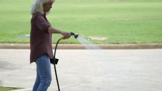 retired woman watering her lawn