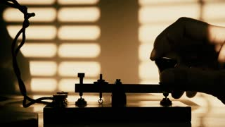 silhouetted hand of a telegrapher sending morse code 4k