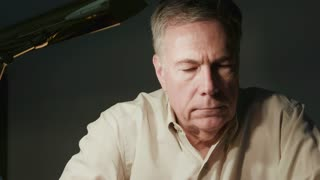 somber man sitting by a desk lamp thinking